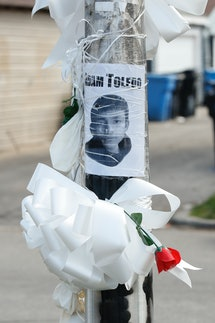 A sign featuring Adam Toledo's face is pasted to a telephone pole, along with a white ribbon and a red rose.