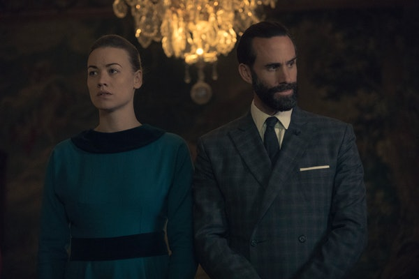 Joseph Fiennes as Commander Fred Waterford and Yvonne Strahovski as Serena Joy Waterford in The Handmaid's Tale Season 3