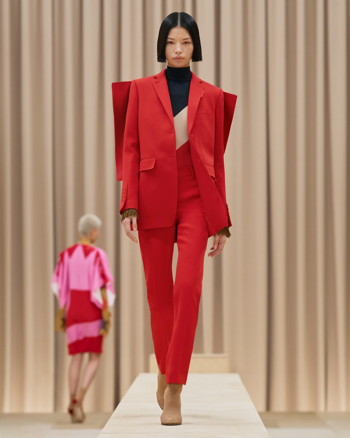 Model walks in Burberry's Fall/Winter 2021 show wearing a red suit.