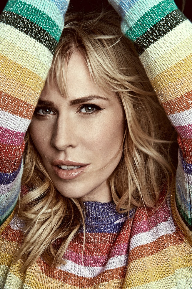 A portrait of Natasha Bedingfield. She wears a rainbow striped sweater and has her arms up framing her face.