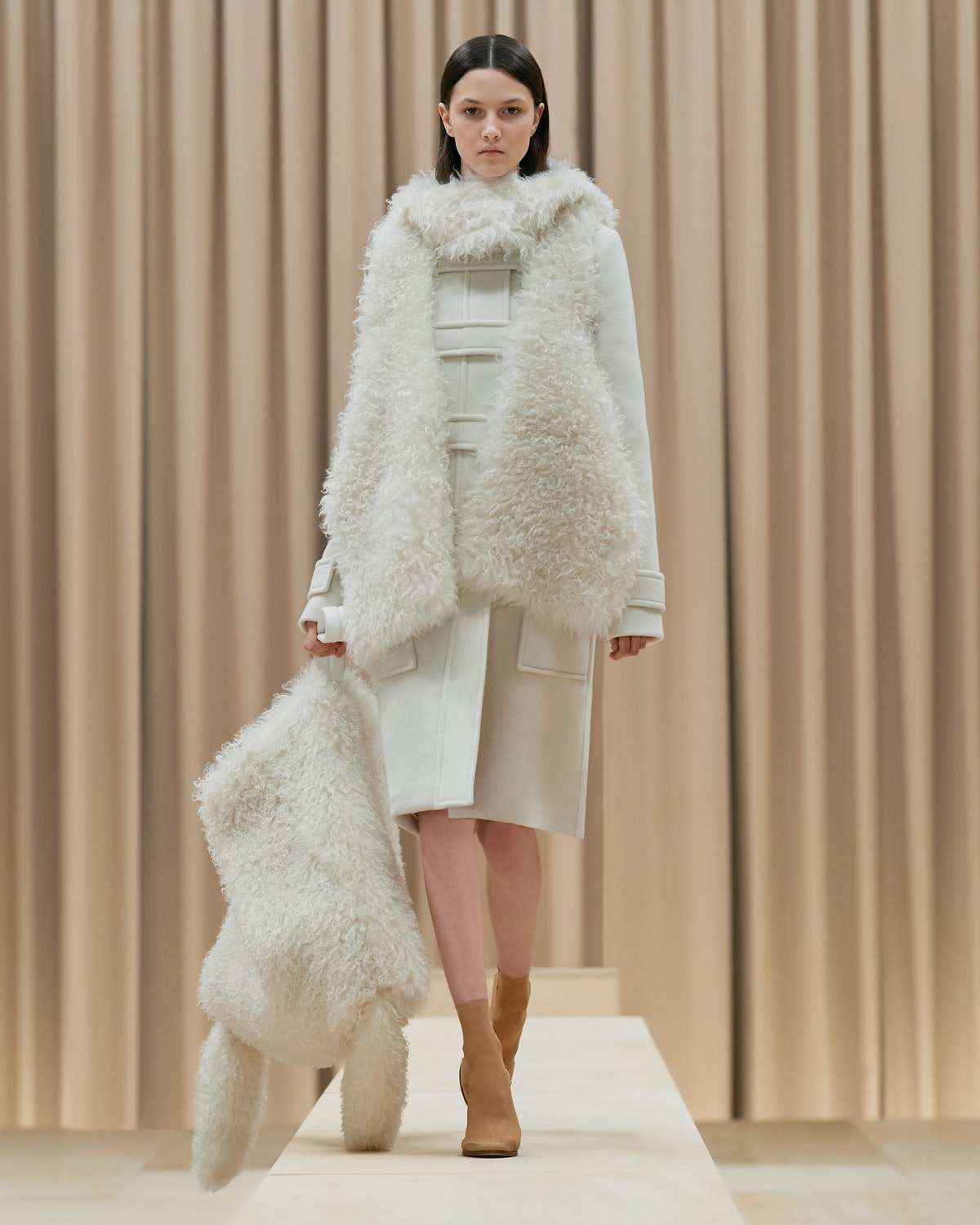 Model walks in Burberry's Fall/Winter 2021 show wearing an all-white outfit.