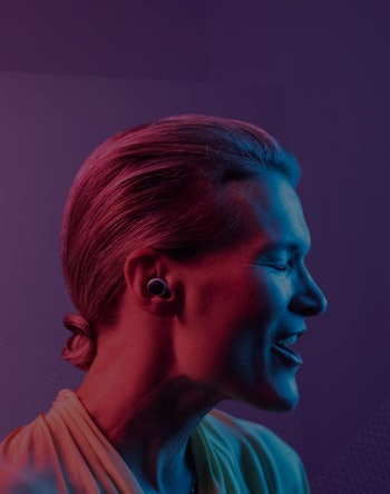A woman is seen under pink, purple, and blue lights with a hearing aid in her ear.