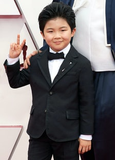 Alan Kim flashing a peace sign on the Oscars red carpet