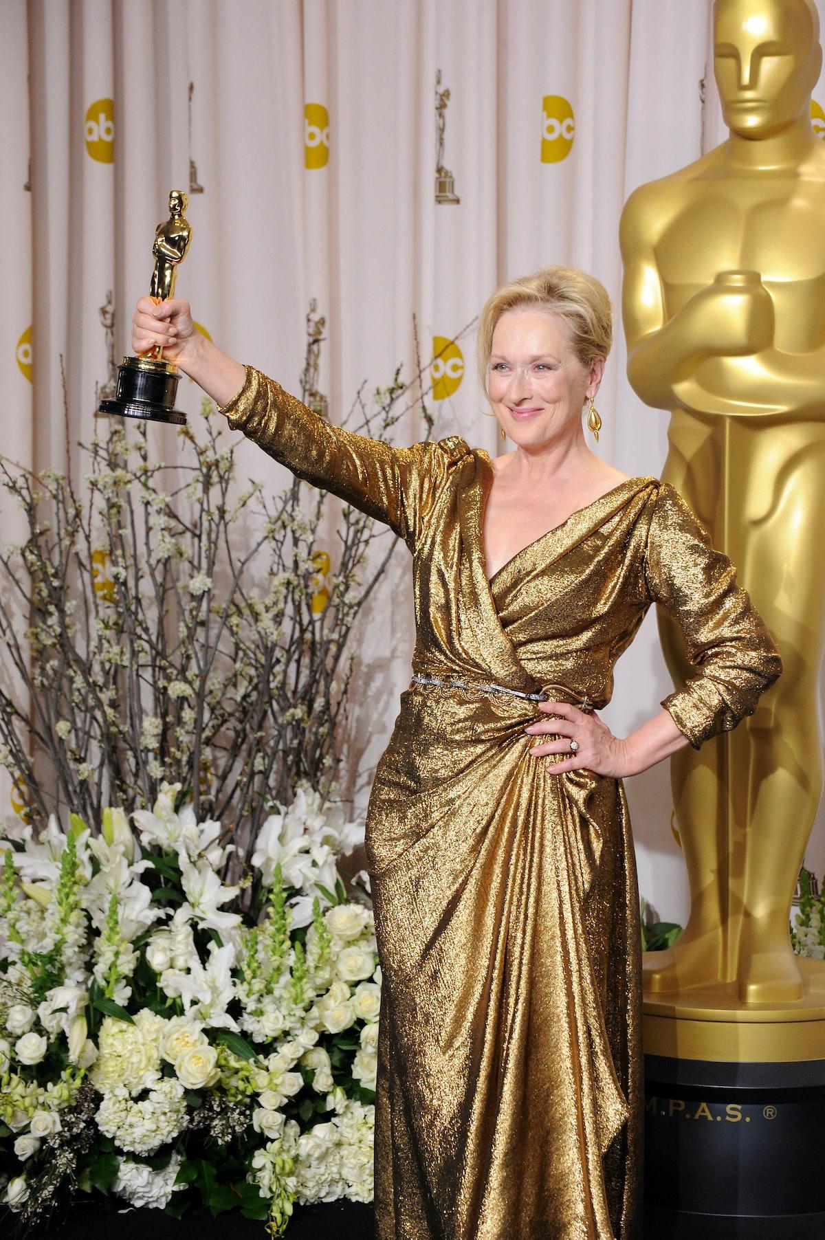 Meryl Streep with Oscar in gold gown.