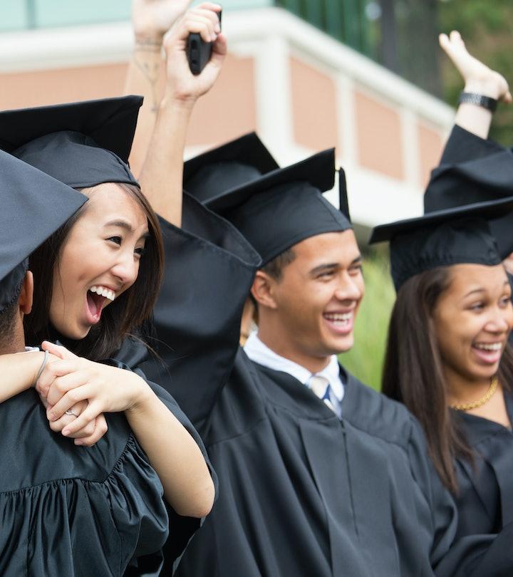 graduates laughing and hugging
