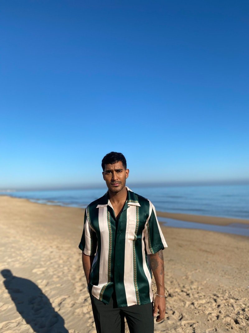 Lee Juggernauth, presenter of Channel 4's A place in the sun pictured on a beach in a stripey shirt