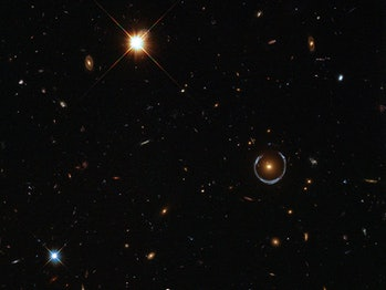 Hubble image shows a deep view of space with a horseshoe-shaped, bluish semi-circle around a bright glowing object visible among the stars and galaxies. Scientists believe the Horseshoe to be a galaxy with a redshift of about 2.4, meaning we see it as it was when the universe was just 3 billion years old.