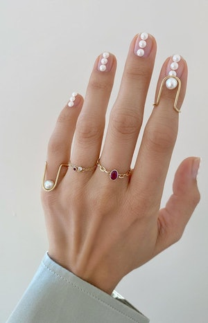 pearls on nails and ruby ring