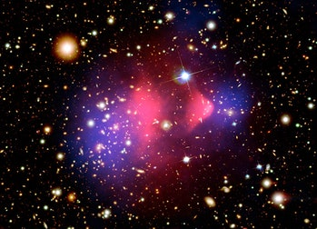 Composite image shows galaxy cluster 1E 0657-556 through multiple wavelengths. Hot gas, shown in pink, has been detected with the Chandra X-ray telescope. Magellan and Hubble provided the optical images of the colliding galaxies. The bulk of the matter in the collision is dark matter, shown in blue and calculated by analyzing the effect of gravitational lensing.