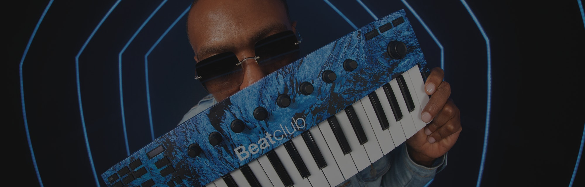 Timbaland holds a molten blue Native Instruments M32 keyboard.