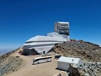 Photo shows the large summit facility building housing the telescope being built atop a mountain nea...