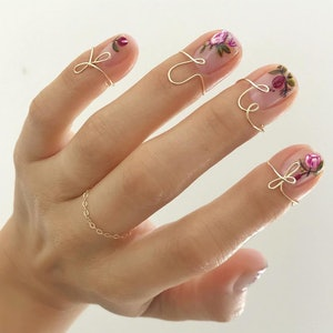 flower-painted nails with gold nail rings