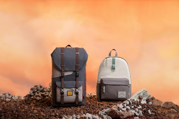 A Baby Yoda and the Mandalorian-inspired backpacks from the Herschel x 'Star Wars' 'The Mandalorian' collection sits on some rocks.