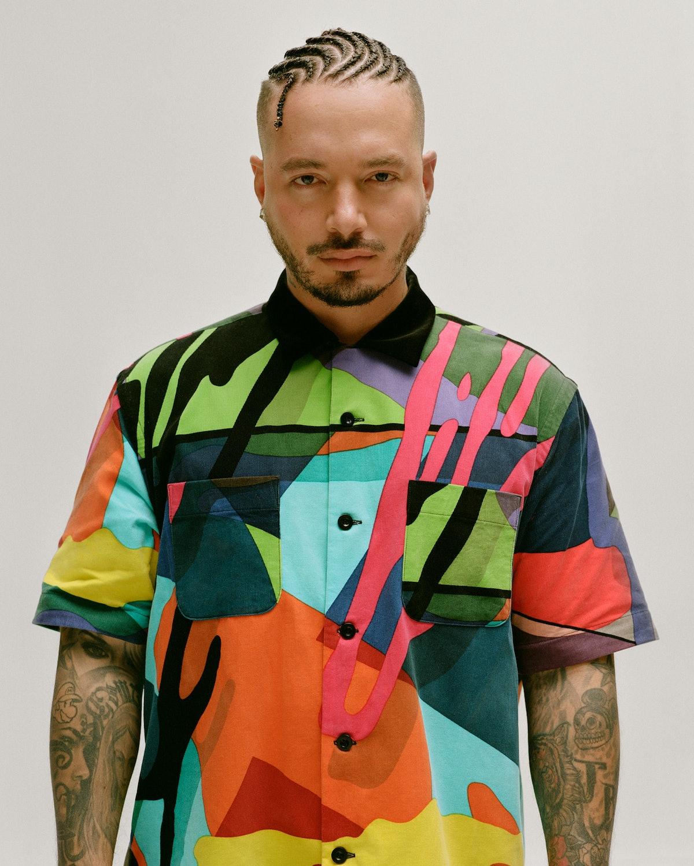 J Balvin wears a Sacai x KAWS shirt; his own earrings (throughout).