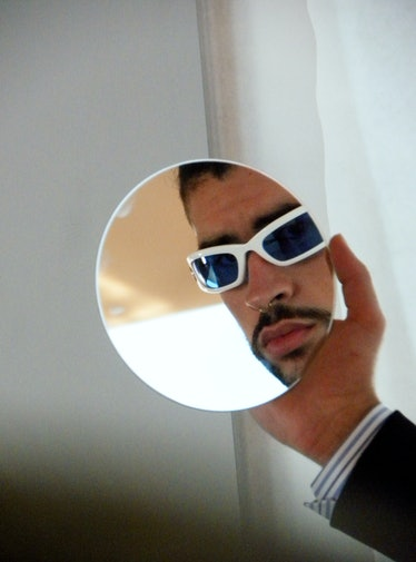 Bad Bunny looks in mirror wearing white sunglasses