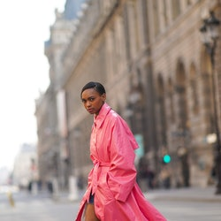 "PARIS, FRANCE - MARCH 09: Emilie Joseph @in_fashionwetrust wears a neon pink long trench shiny coat from Margiela, white wool socks with the printed cartoon ""Denver The Last Dinosaur"" from Citadium, Valentino bronze shiny sneakers shoes, on March 09, 2021 in Paris, France."