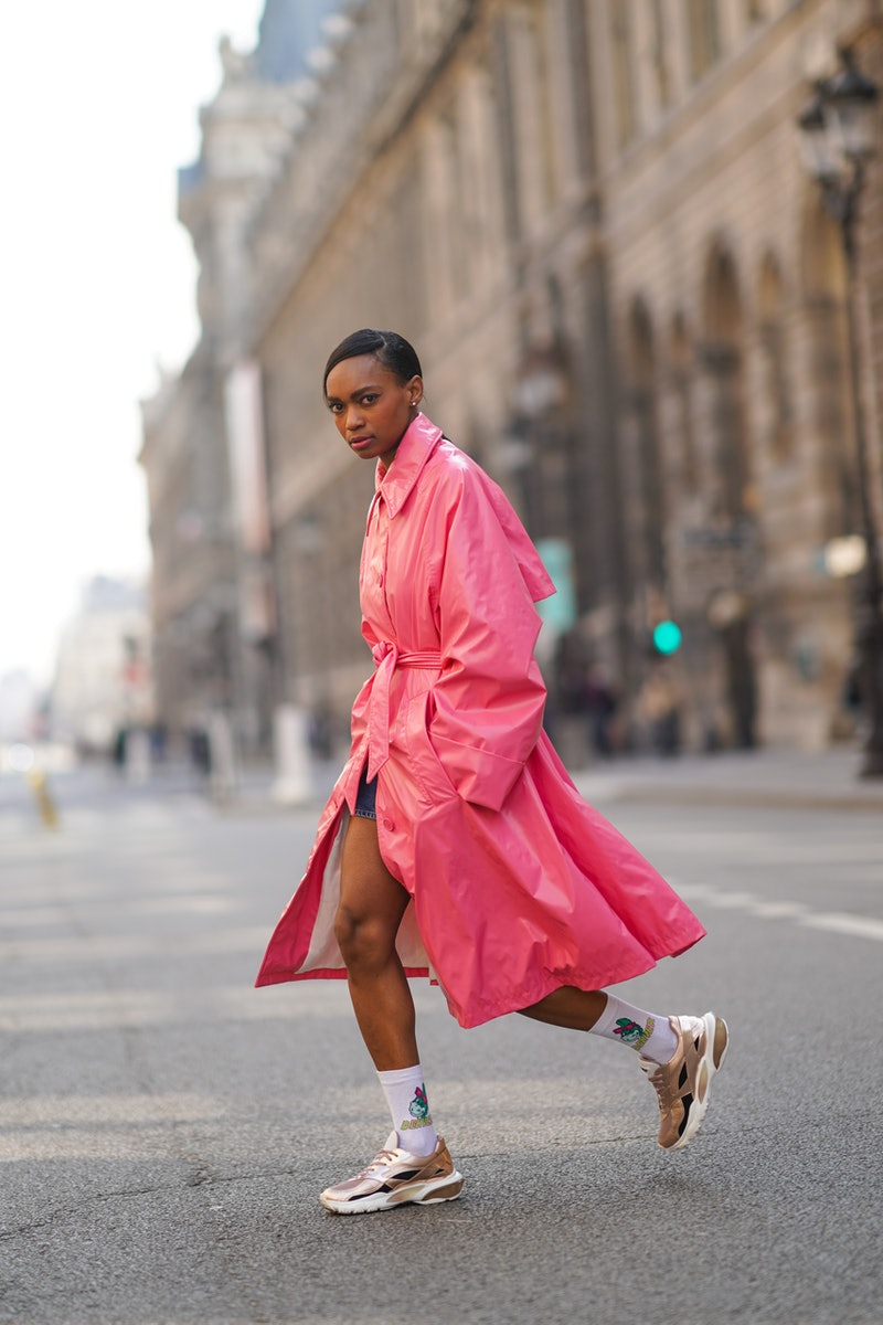 """PARIS, FRANCE - MARCH 09: Emilie Joseph @in_fashionwetrust wears a neon pink long trench shiny coat from Margiela, white wool socks with the printed cartoon """"Denver The Last Dinosaur"""" from Citadium, Valentino bronze shiny sneakers shoes, on March 09, 2021 in Paris, France."""