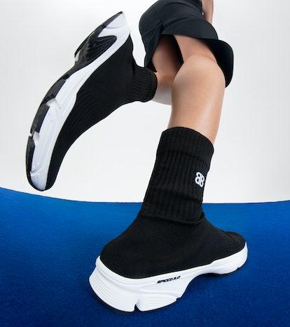 Model wearing Balenciaga black sneakers.