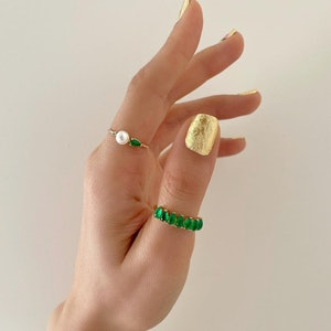 gold nail polish with pearl and jade rings modeled on hand