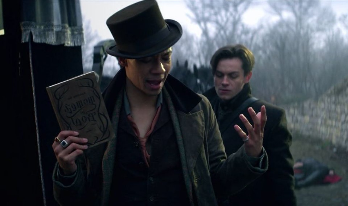 Kit Young as Jesper holding a copy of Shadow and Bone in Shadow and Bone