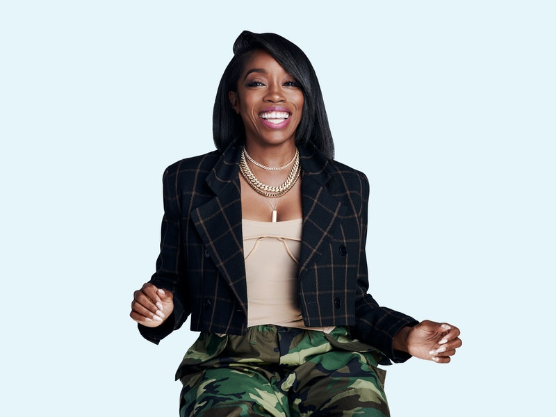 Singer Estelle pictured smiling wearing a checked jacket and camo trousers