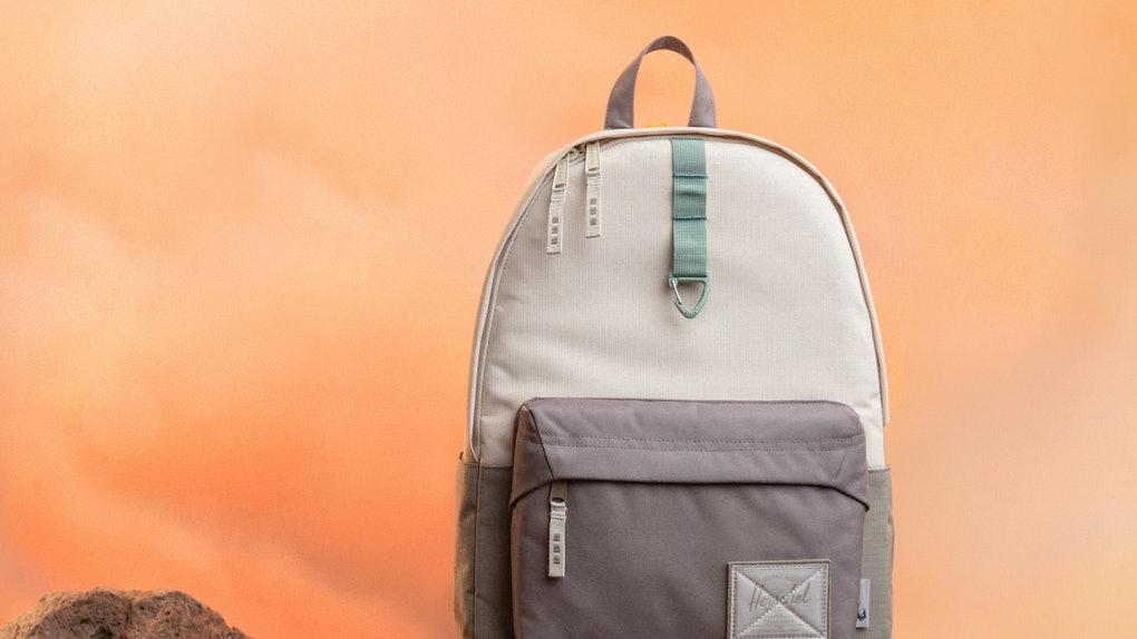 A Baby Yoda-inspired backpack from the Herschel x 'Star Wars' 'The Mandalorian' collection sits on some rocks.