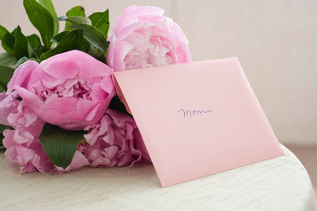 "Small bouquet of peonies with pink greeting card envelope that says ""mom"" propped up against them"