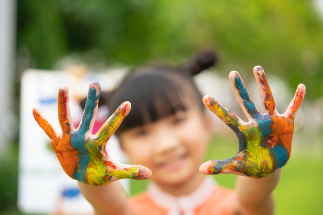 Little girl holding up her paint-covered hands