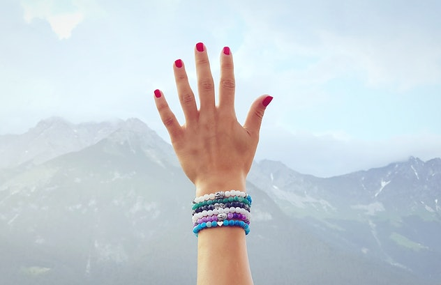 Arm reaching into the sky with several bead bracelets on the wrist