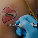 """A close-up of an in-progress tattoo on a person's arm that reads, """"Mom"""""""