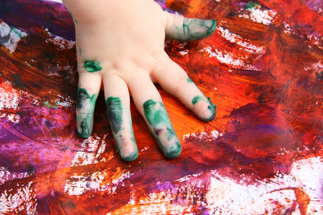 Close up of toddler hand finger-painting
