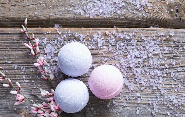 Three bath bombs, pastel colors, sitting on wood floor