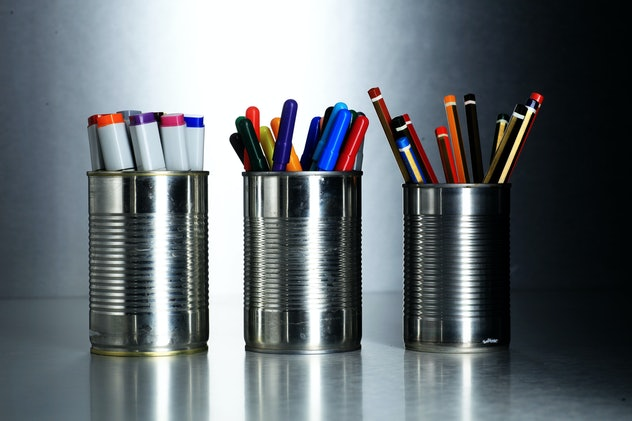 Three tin cans holding pencils and pens, sitting in a row