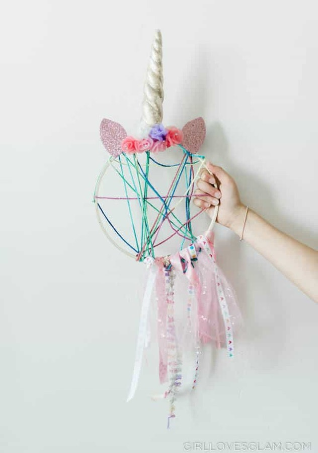 Hand holding out dream catcher with unicorn horn, ears, and ribbons hanging from it
