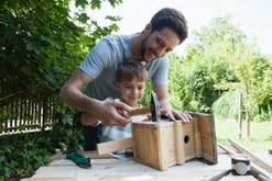 Dad and son making homemade bird house