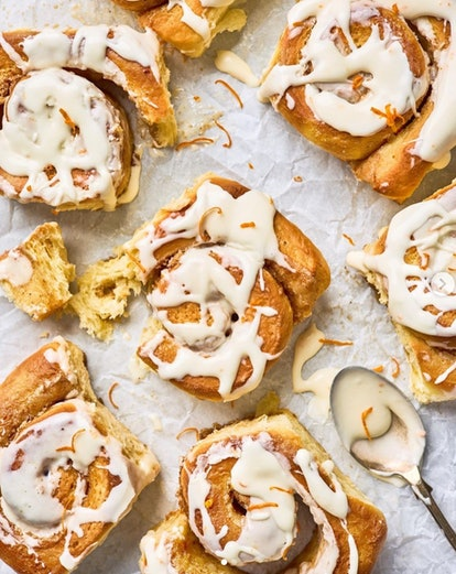 Close-up of orange mimosa cinnamon rolls with icing drizzled on top