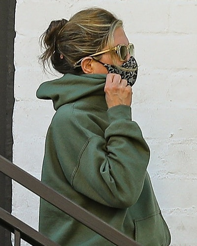 Jennifer Aniston covers her face with a mask while leaving a skincare salon in Beverly Hills with her bodyguard.