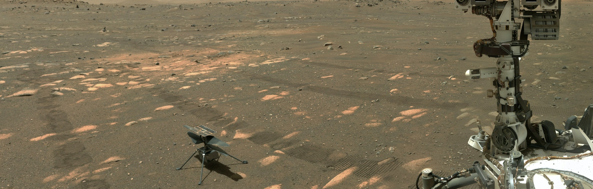 NASA's Perseverance Mars rover took a selfie with the Ingenuity helicopter, seen here about 13 feet (3.9 meters) from the rover in this image taken April 6, 2021, the 46th Martian day, or sol, of the mission by the WATSON (Wide Angle Topographic Sensor for Operations and eNgineering) camera on the SHERLOC (Scanning Habitable Environments with Raman and Luminescence for Organics and Chemicals) instrument, located at the end of the rover's long robotic arm.