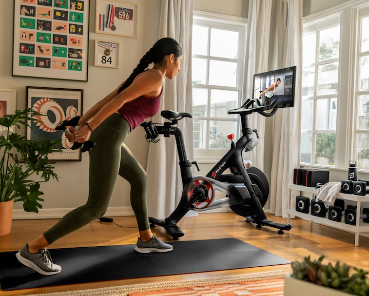 A woman is seen working out next to a Peloton bike in her apartment.