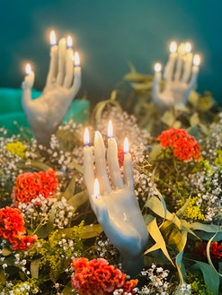 lit hand candle with a background of flowers