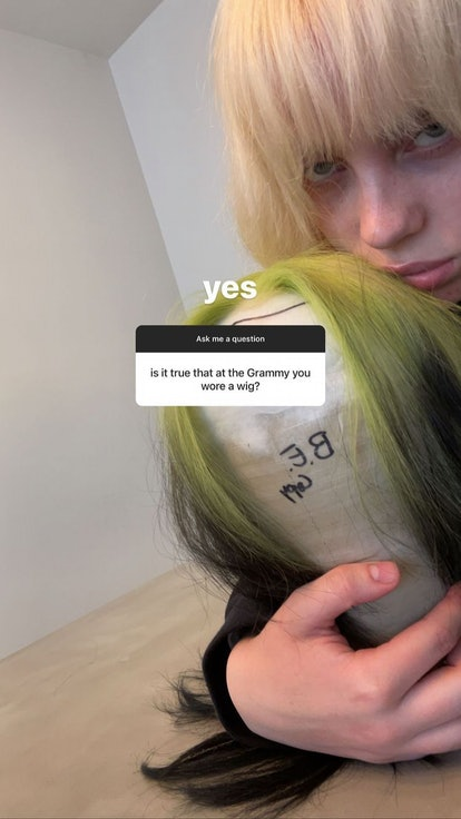 Billie Eilish with platinum blonde hair holds the black and green wig she wore to the Grammys 2021