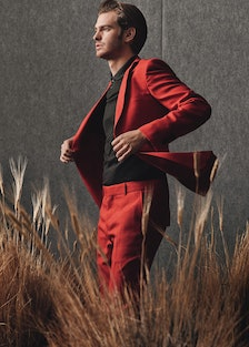 Andrew Garfield in a red suit looking at something in the distance.