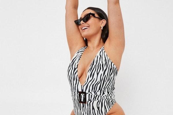 A plus-size model wears a plus-size, zebra swimsuit from Nasty Gal.