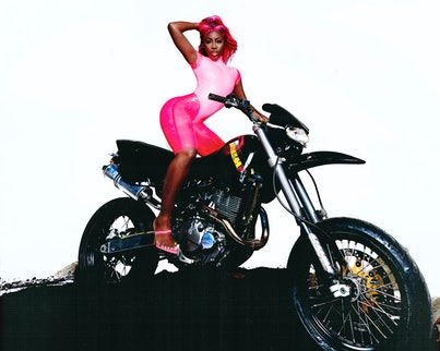 A portrait of Bree Runway in a skintight pink catsuit posing on a motorcycle.