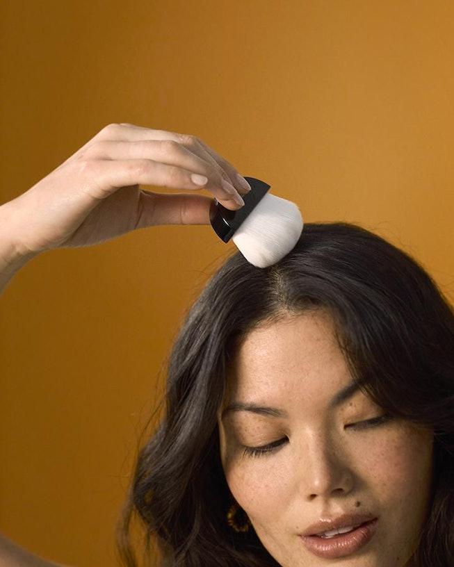 Person runs brush from Crown Affair Dry Shampoo through hair
