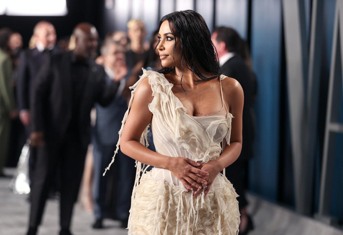 Kim Kardashian on a red carpet in artfully tattered dress.