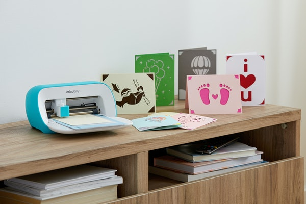 The Cricut Joy sits on a desk next to DIY cards made from it.