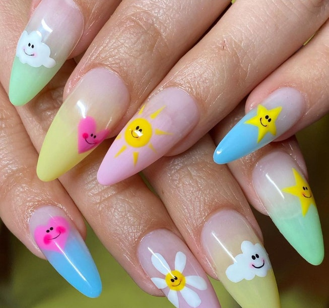 Two hands rest atop one another, showing nails that feature daisy flowers, clouds, hearts, and stars...