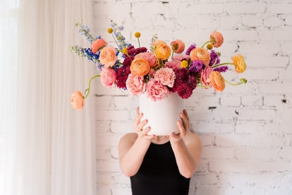 a woman holds a bouquet of flowers in a white bucket, including blue snapdragon, peach ranunculus and peach roses