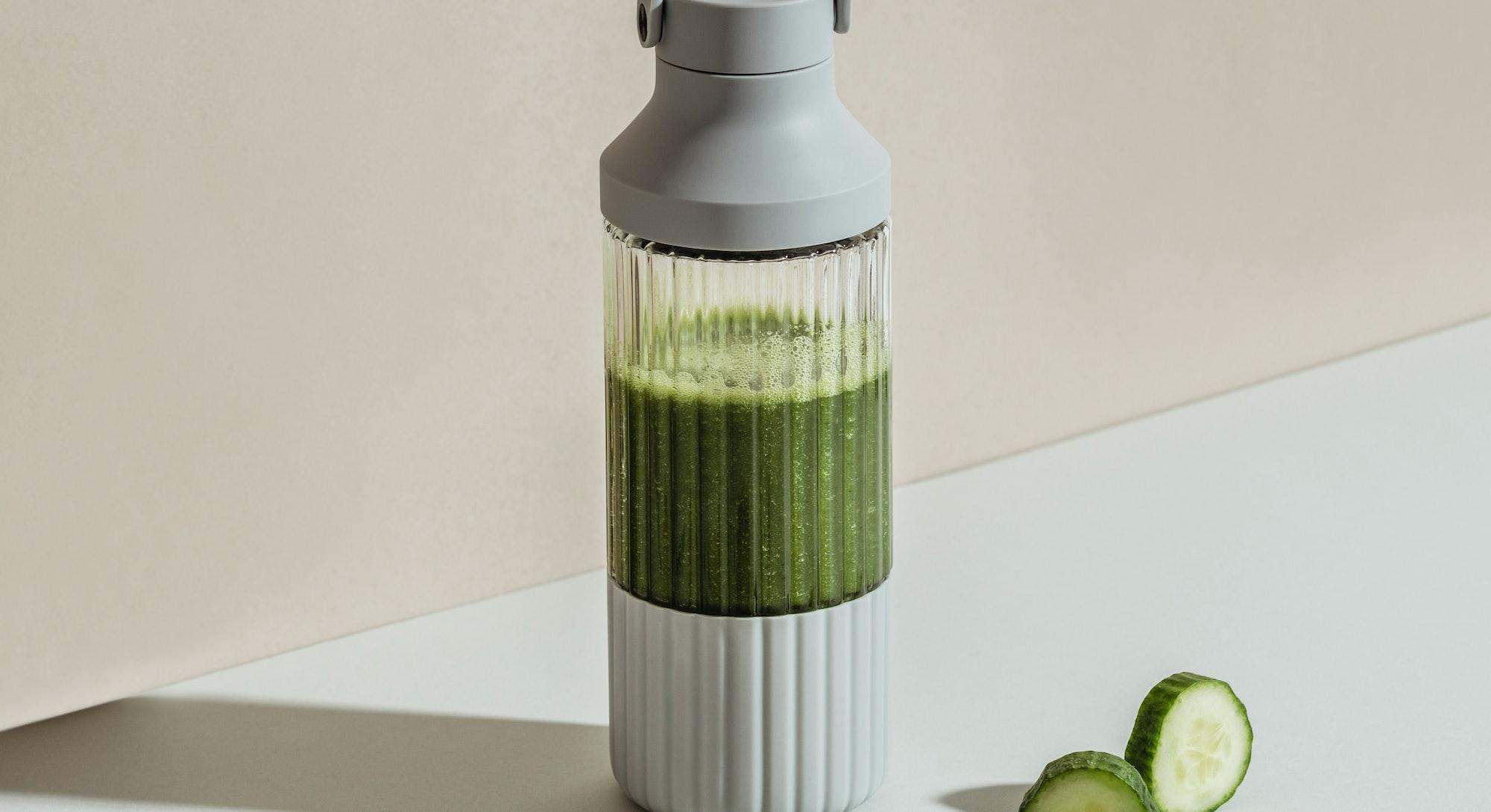 A green smoothie can be seen inside a sleek design B10 blender.